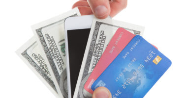 hand holding credit cards, cash, and phone